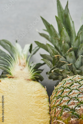 selective focus of whole and half of pineapple on grey background