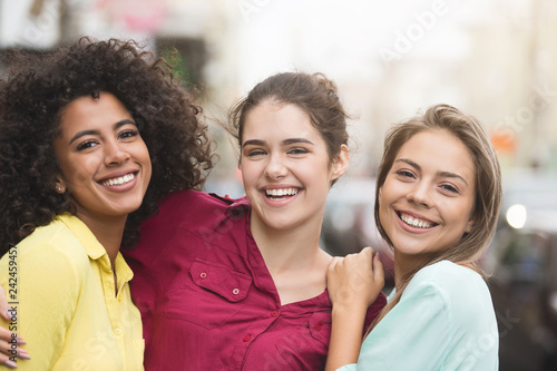 Diverse friends hugging and laughing on the street - 242459457