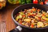 Fried pan vegetables, with mushrooms and dried tomatoes. Seasoned with a mix of herbs. - 242461458