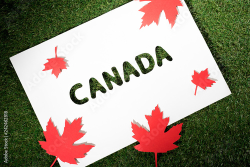 white board with cut out word 'canada' on green grass background with maple leaves