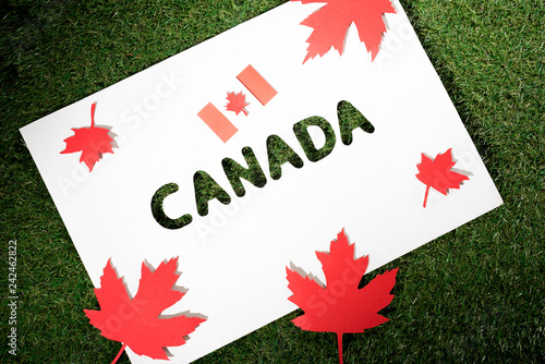white board with cut out word 'canada' on green grass background with maple leaves and canadian flag