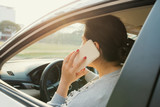 Woman driver using her mobile phone while driving car - 242463024