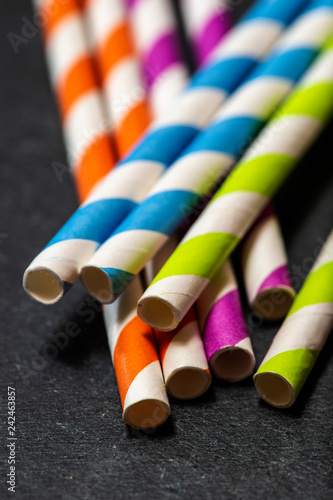 Multicoloured drink straws on dark stone background. Vibrant colours contrast on natural light.