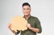 Leinwandbild Motiv Smiling young asian man holding speech bubble on grey background