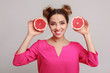 Leinwanddruck Bild - Happy woman with halves of grapefruits against background