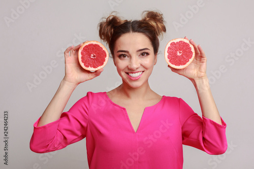 Leinwanddruck Bild Happy woman with halves of grapefruits against background