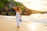 Stress free woman in white summer dress walking on the beach at sunset - 242469429