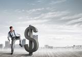 Determined banker man against modern cityscape breaking dollar cement figure - 242472016