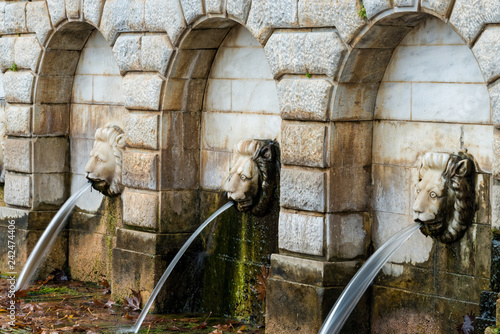 Traditional marble drinking fountain with heads of lions in the village of Agios Vassilios in Peloponnese , Greece