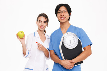 Confident young multiethnic doctors couple standing