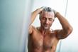 Leinwanddruck Bild - Handsome young man washing hair while taking shower at home