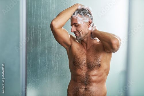 Leinwanddruck Bild Handsome young man with beautiful muscular body washing his hair