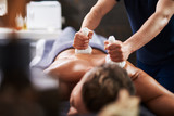 Young man having Ayurveda procedure at wellness center - 242481835