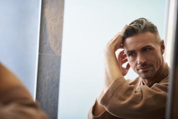 Handsome young man looking in the mirror at bathroom