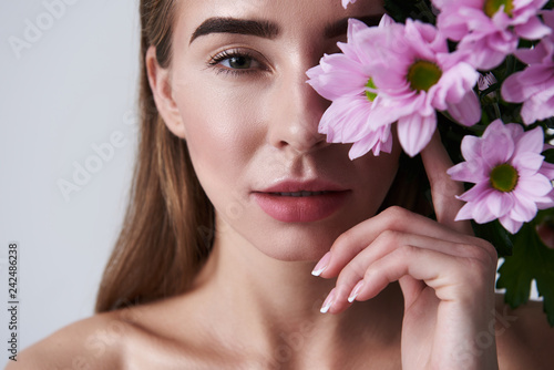 Leinwandbild Motiv Attractive young woman covering eye with beautiful pink flowers