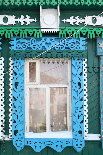 Foto Murales Windows with carved frames on wooden house in Russian village