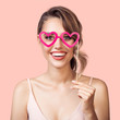 Portrait of cheerful smiling woman holding paper party glasses heart in hand. Pink background.
