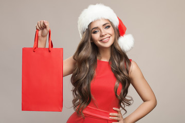 Portrait of attractive cute woman in santa hat holding shopping bag. Gray background.