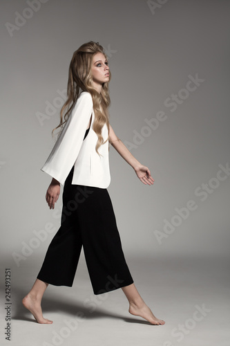 Leinwanddruck Bild Fashion portrait of blonde woman dressed white jacket and black breeches.