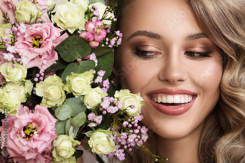 Leinwanddruck Bild Close up portrait of beautiful smiling woman. Flowers near her face.