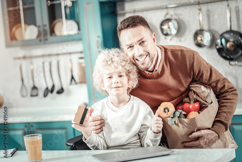 Delighted male person embracing his son with love