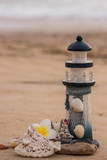 Beautiful decor in the form of a lighthouse and seashells on the sand with space for the text - 242496232