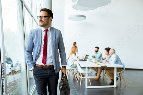 Poster Young businessman leaves a meeting while other people stay in office