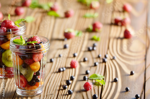 Assorted berries in mason jar on kitchen wooden table - 242501254