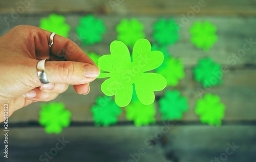 Beautiful close-up of woman hand holds a green irish shamrock with a pile of feast clovers over wooden tables as background bokeh that remind luck - 242502023