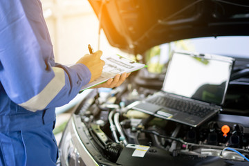 car service, repair, maintenance concept - auto mechanic man or Smith writing to the clipboard at warehouse workshop, technician doing the checklist for repairs engine a car in the garage with laptop