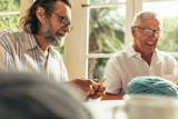 Senior beard man knitting with friend sitting by - 242507457