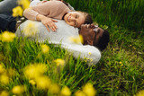 Beautiful young couple lying in green grass - 242508401