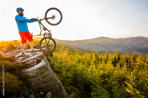 Mountain biker riding on bike in spring mountains forest landscape. Man cycling MTB enduro flow trail track. Outdoor sport activity. - 242511270