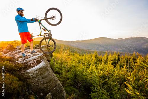 Leinwandbild Motiv Mountain biker riding on bike in spring mountains forest landscape. Man cycling MTB enduro flow trail track. Outdoor sport activity.