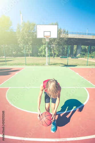 happy teenager play basketball outdoor - healthy sporty teenagers lifestyle concept in spring or summer time