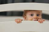 portrait of cute little baby boy peeking from cot - 242515690