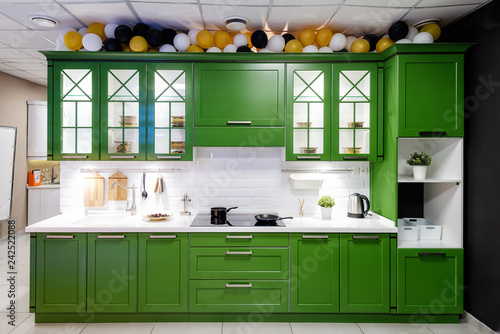 Classic kitchen interior with green trim. Kitchen acrylic countertop with built-in sink.