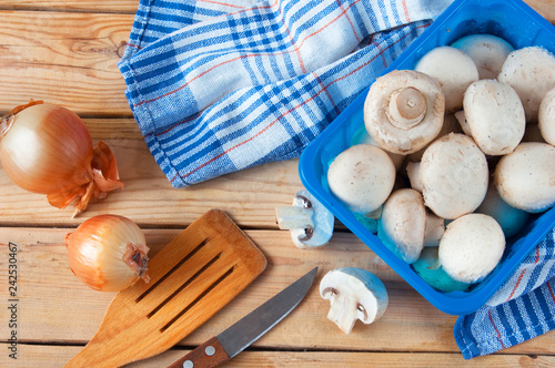 Champignon mushrooms cooking with onion on wooden background, cutting and frying mushrooms - 242530467