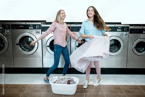Two happy girlfriends having fun dancing together while washing in the self-service laundry