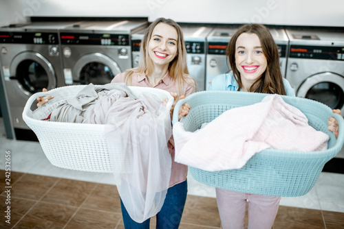 Portrait of a two cheerful girlfriends standing together with baskets full of clothes for washing in the self-service laundry