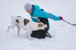 Quadro Mature woman playing with mixed breed dog hiding a rope at winter season