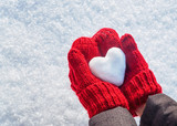Female hands in knitted mittens with heart of snow in winter day. Love concept. Valentine day background. - 242535039