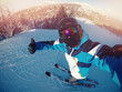 Winter extreme sport with selfie action camera. Man rides on slopes skis in protective helmet