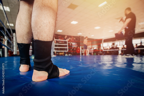 MMA fighter prepares to fight in ring, close-up legs in socks.