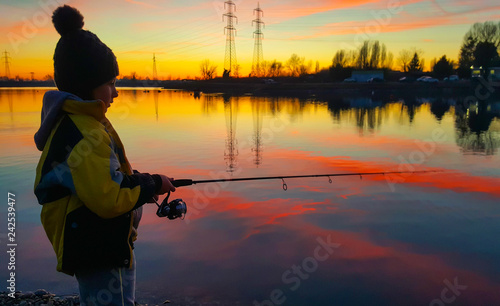 obraz lub plakat young girl fishing in a pond at sunset