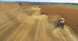 Combine Harvesters on Wheat field aerial view 4k video. Flight over Harvest agriculture farm rural landscape. Farming production - 242544244