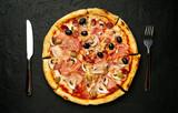 Tasty pizza on black concrete  background.