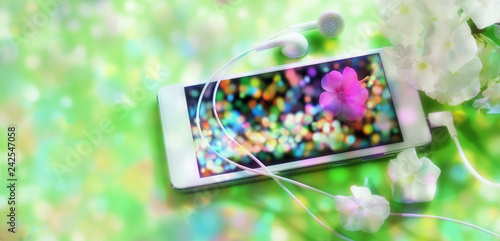 music search. smartphone white earphone pink white flower lies on the screen green multicolored bokeh background - 242547058