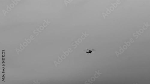 Slow motion black and white footage of helicopter flying and spinning rotors.