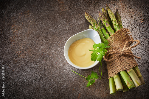 Bunch of fresh green asparagus and bowl of sauce